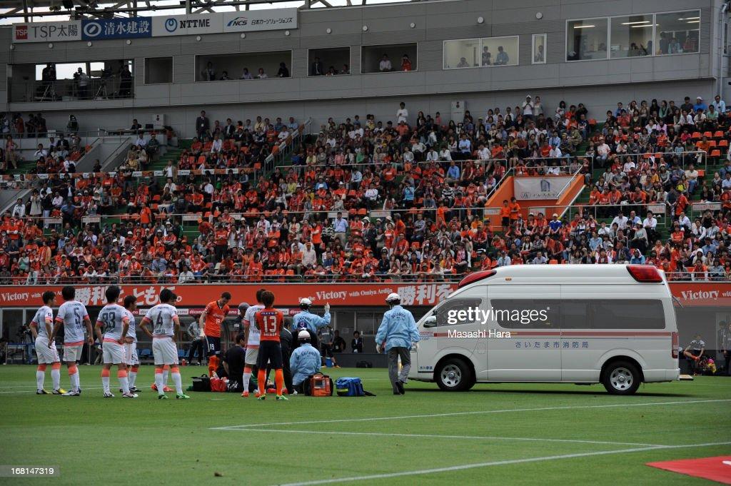 An ambulance drives onto the pitch asTakamitsu Tomiyama #28 of Omiya Ardija (R) lies on the ground after colliding during the J.League match between Omiya Ardija and Sanfrecce Hiroshima at Nack 5 Stadium Omiya on May 6, 2013 in Saitama, Japan.