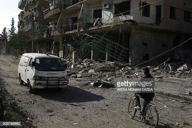An ambulance drives past heavily damaged buildings following reported air strikes in Hammuriyeh in the rebelheld Eastern Ghouta area on the outskirts...