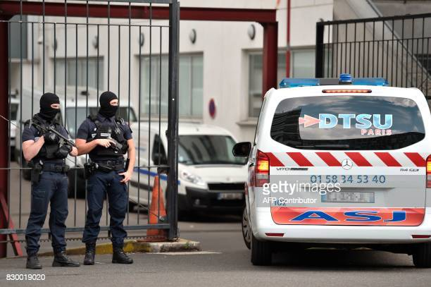 An ambulance enters as French special police officers stand guard at the entrance of the Georges Pompidou Hospital in Paris on August 11 where the...
