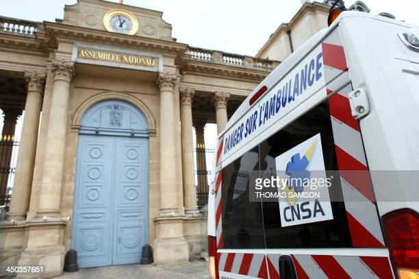 An ambulance is parked in front of an entrance of the French National Assembly on November 18 2013 in Paris as paramedics stage a protest against a...