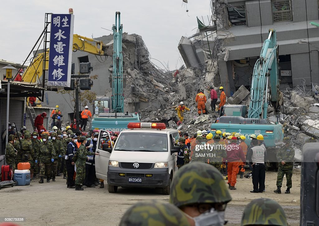 An ambulance is standing by in front of the Wei-Kuan complex which collapsed in the 6.4 magnitude earthquake, in the southern Taiwanese city of Tainan on February 10, 2016. The developer of a Taiwan apartment complex that collapsed during a strong earthquake was arrested February 9, as rescuers reported hearing signs of life in the rubble where some 100 people are still trapped. / AFP / SAM YEH