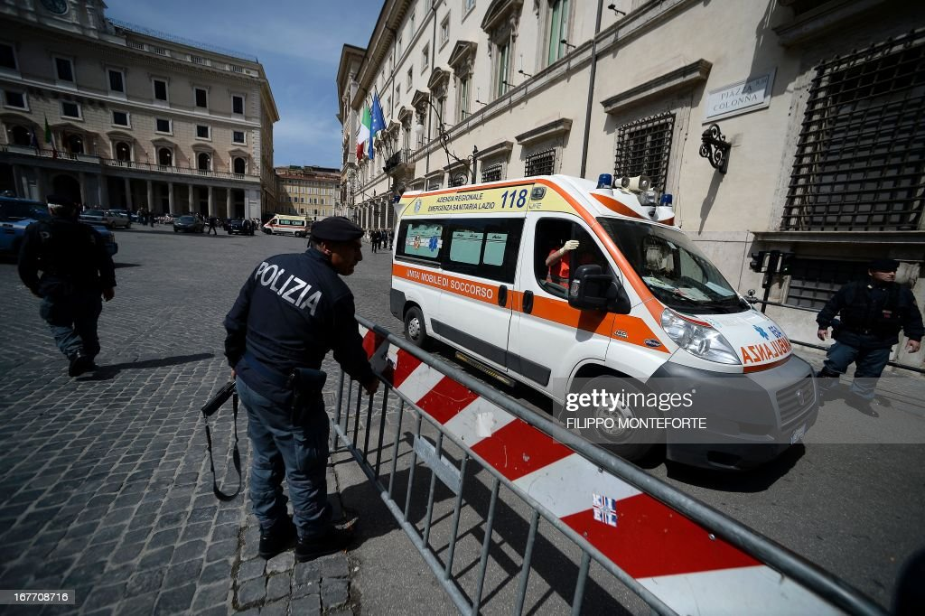 An ambulance leaves the area where a Carabiniere police officer was shot by an apparently disturbed man, on April 28, 2013 in Rome, outside the palazzo Chigi, the Italian Prime minister offices, while the country's new ministers were being sworn in. Two policemen were wounded, as well as a passerby, in the shooting. The attacker, named by Italian media as businessman Luigi Preiti, 49, was tackled to the ground by by police as witnesses fled the scene.