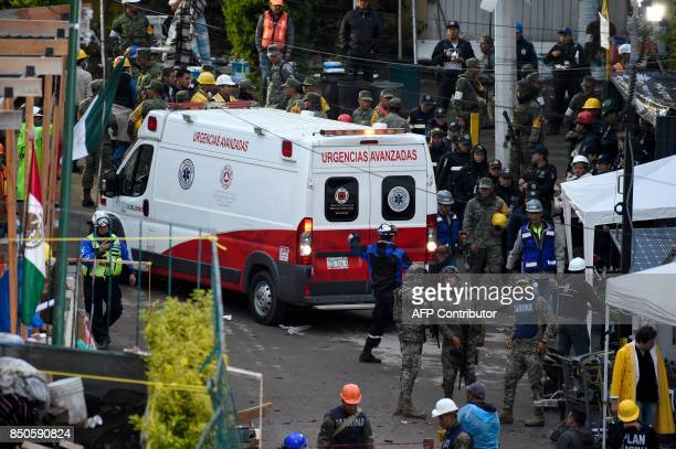 An ambulance maneuvers as rescuers firefighters policemen soldiers and volunteers search for survivors in a flattened building in Mexico City on...