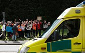 An ambulance passes demonstrators and junior doctors holding placards as they protest outside the Basingstoke and North Hampshire Hospital in...
