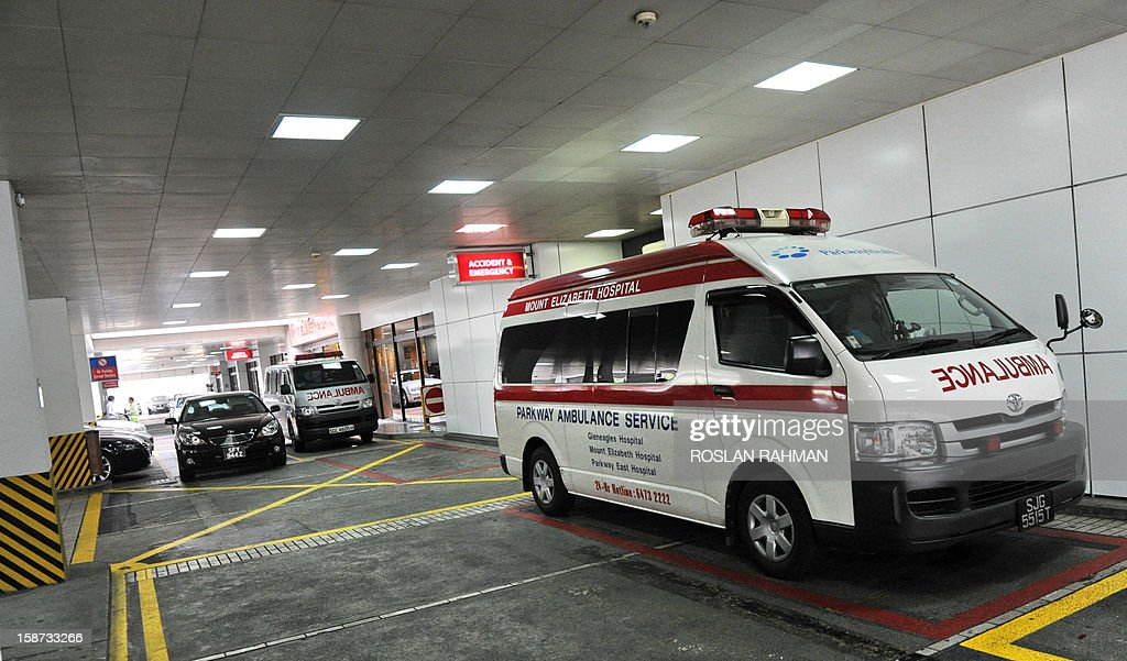 An ambulance (R) sits parked outside the accident and emergency entrance of Mount Elizabeth Hospital in Singapore on December 27, 2012. An Indian student who was left fighting for her life after being brutally gang-raped in New Delhi was being flown to Singapore for treatment at Mount Elizabeth, doctors and a report said late on December 26. AFP PHOTO / ROSLAN RAHMAN