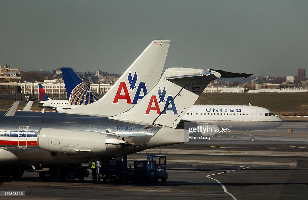 An American Airlines Inc. McDonnell Douglas MD-82 plane sits parked at a gate while a United Continental Holdings plane taxis down the runway at LaGuardia Airport in the Queens borough of New York, U.S., on Wednesday, Nov. 21, 2012. U.S. travel during the Thanksgiving holiday weekend will rise a fourth straight year, gaining 0.7 percent from 2011, as trips by automobile rise even as airplane trips decline, AAA said last week. Photographer: Michael Nagle/Bloomberg via Getty Images