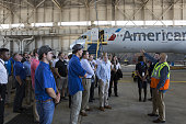 An American Airlines Inc staff member speaks with attendees on a tour of an airport hangar at DallasFort Worth International Airport during a...