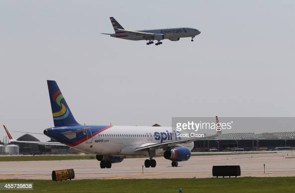 An American Airlines jet prepares to land as a Spirit Airlines jet taxis at O'Hare International Airport on September 19 2014 in Chicago Illinois In...