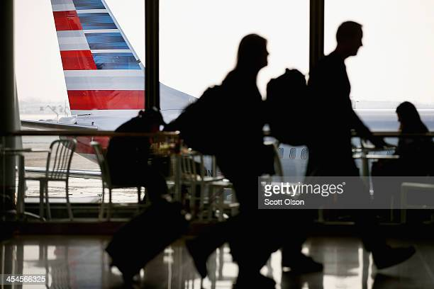 An American Airlines jet with the company's new tail logo sits at a gate at O'Hare Airport on December 9 2013 in Chicago Illinois American Airlines...