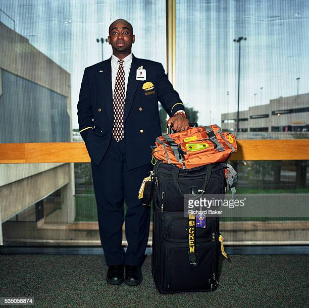 An American Airlines male flight attendant stands with his crew baggage against a window at Dallas Fort Worth airport Texas Dressed in the corporate...