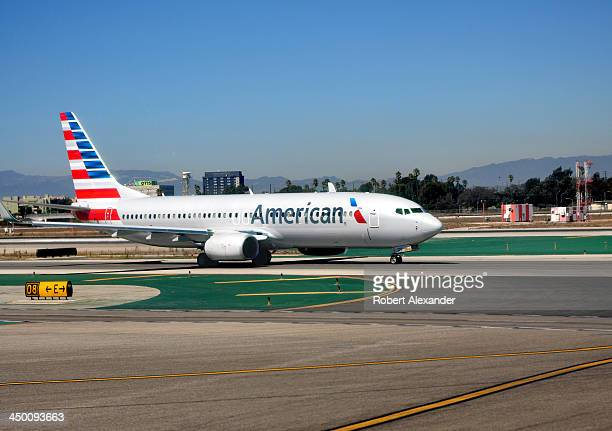 An American Airlines passenger jet taxis toward the gate at Los Angeles International Airport