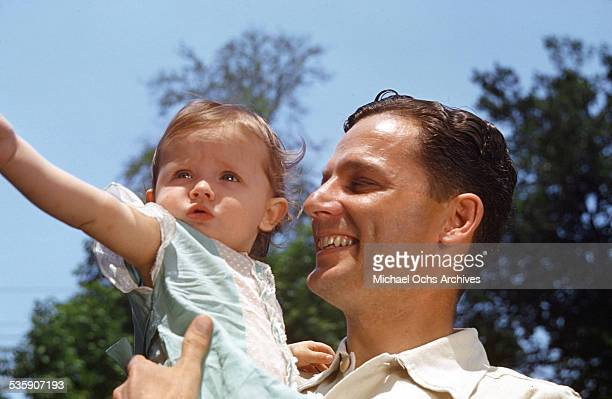An American Airlines pilot holds his little toddler at home