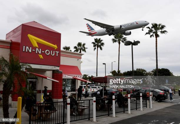 An American Airlines plane flies over a fast food restaurant as it prepares to land at Los Angeles International Airport in Los Angeles California on...