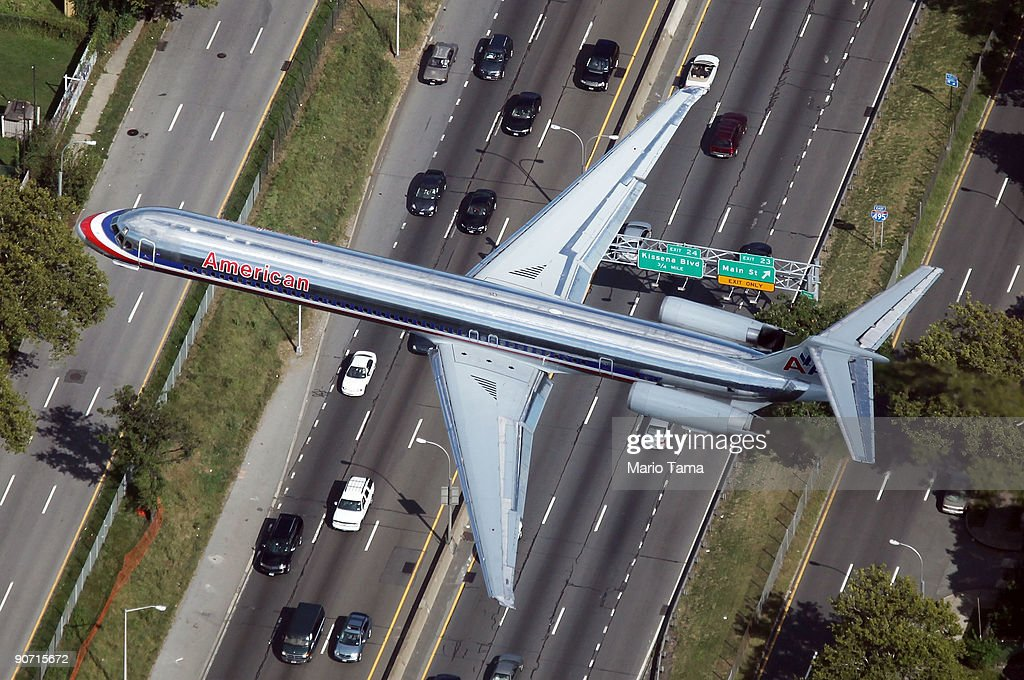 An American Airlines plane flies over a highway September 13, 2009 in the Queens borough of New York City.