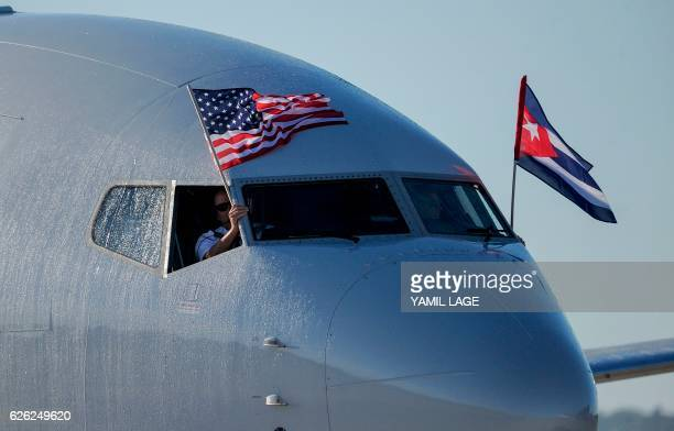 TOPSHOT An American Airlines plane fluttering US and Cuba national flags is seen uppon arrival at Jose Marti International Airport becoming the first...