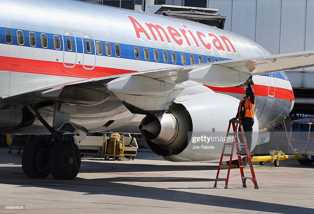 An American Airlines plane is parked at a gate at the Miami International Airport on February 7, 2013 in Miami, Florida. Reports indicate that a deal between American Airlines and US Airways to merge may be set for early next week. If the deal goes through it would create the world's biggest airline.