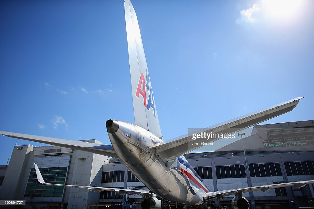 An American Airlines plane is seen parked at a gate at the Miami International Airport on February 7, 2013 in Miami, Florida. Reports indicate that a deal between American Airlines and US Airways to merge may be set for early next week. If the deal goes through it would create the world's biggest airline.