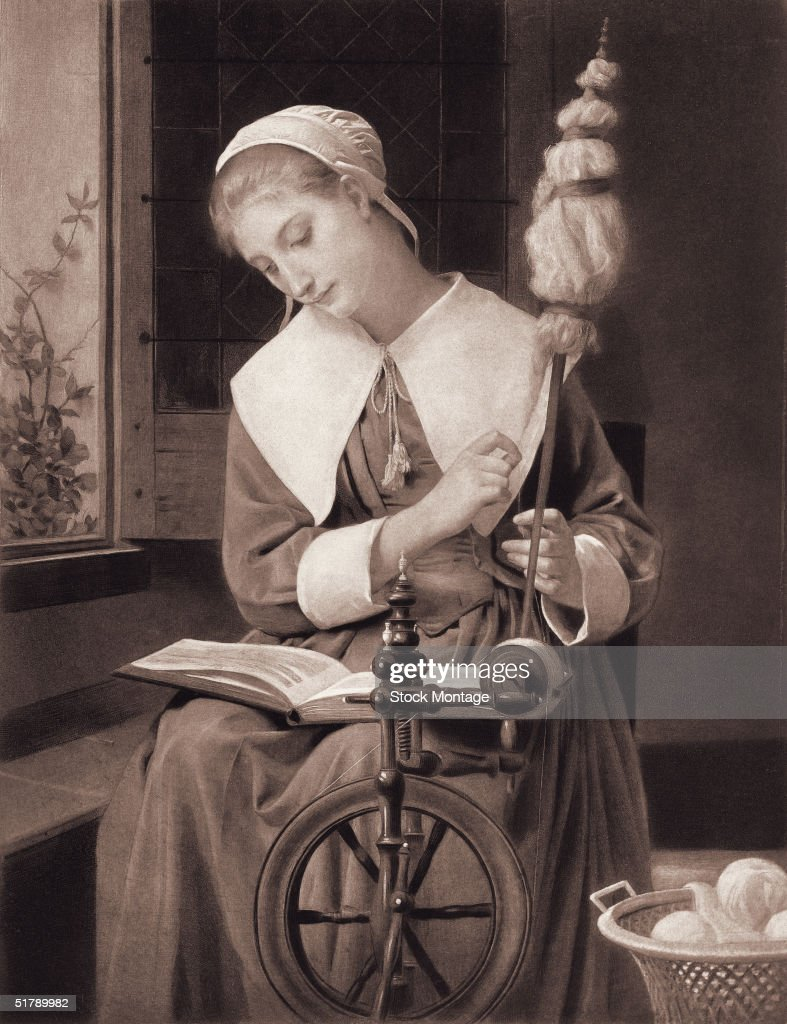 An American colonialera woman reads a book as she spins yarn on a spinning wheel 1700s