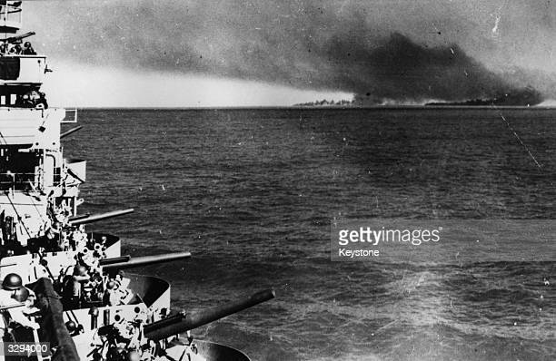 An American cruiser of the invasion fleet and Licata Sicily blazing in the background