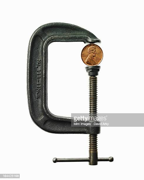 An American currency coin in a metal clamp. Cent.