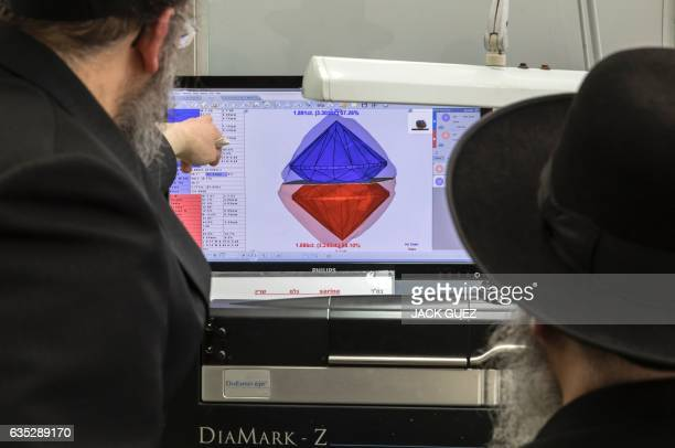 An American diamond buyer evaluates a rough cut diamond in a scanner to analyse the possibilities of transformations during the International Diamond...