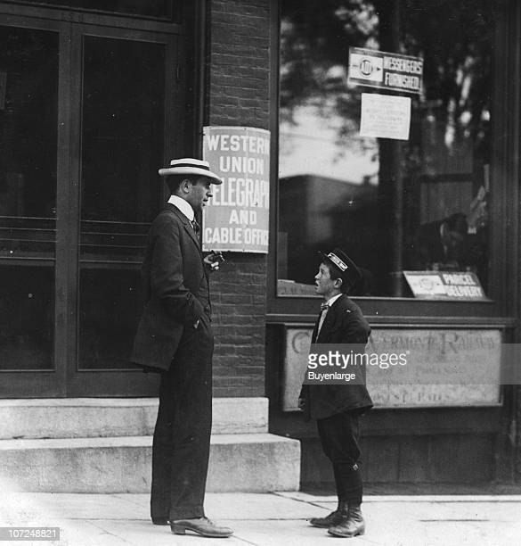 An American District Telegraph boy listens to a man outside a Western Union office 1910 He typically works from noon until 1030 pm