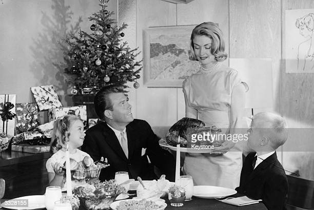 An American family admire a turkey their mother is bringing to the table A small Christmas tree with presents is in the background