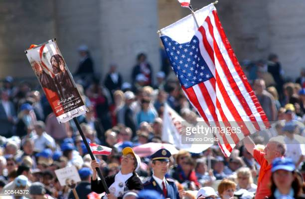 An American flag and a banner showing the portrait of a new Saint Nimatullah Kassab Al Hardini as shown in St Peter's Square during a canonization...