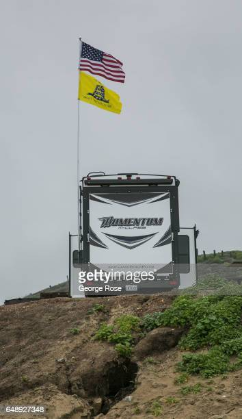 An American flag and a 'Don't Tread On Me' flag fly over a motorhome recreational vehicle parked a beach campsite on February 8 in Jalama Beach...