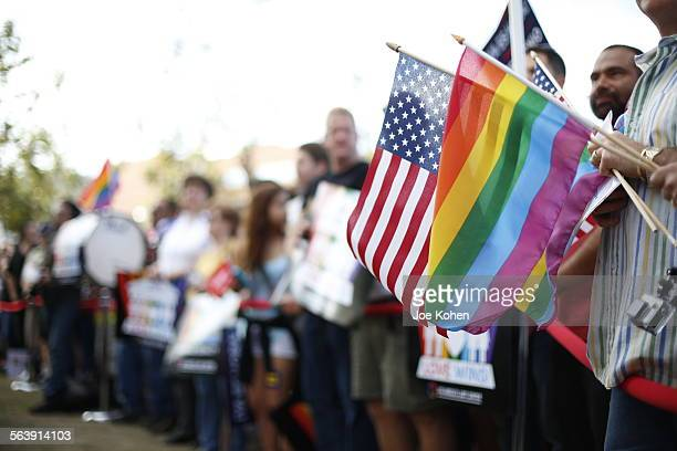 An American flag and a pride rainbow flag overlap in the crowd during Tsamesex marriage support rally in West Hollywood celebrate the Supreme Court's...