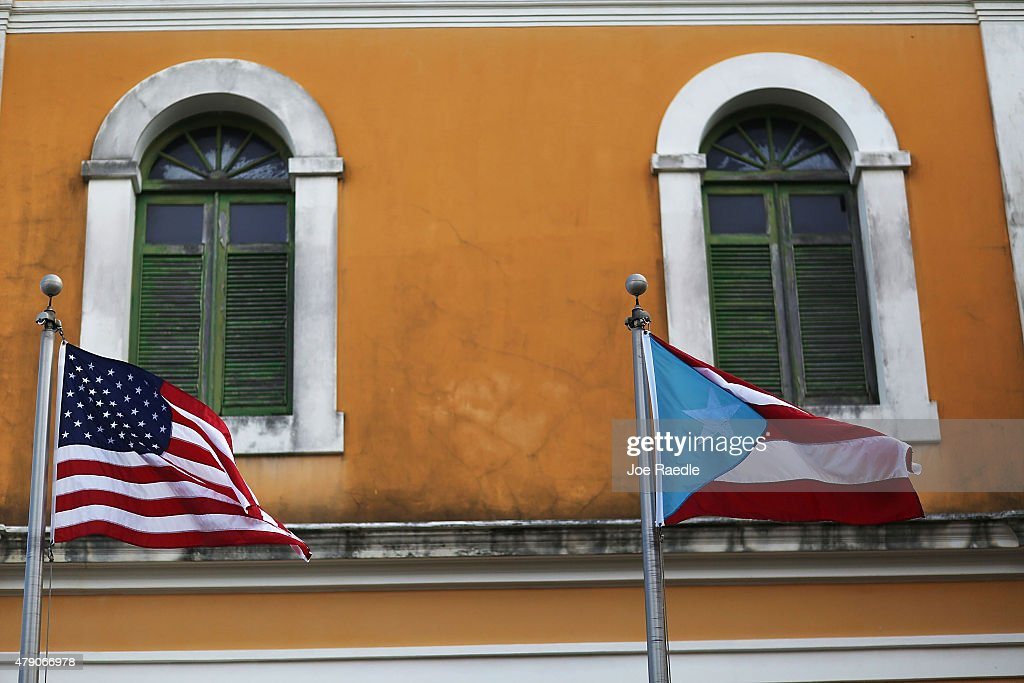 An American flag and Puerto Rican flag fly next to each other in Old San Juan a day after the Puerto Rican Governor Alejandro Garcia Padilla gave a...