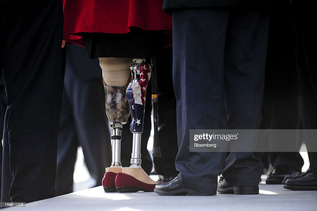 An American flag design is seen on one of the prosthetic legs of Representative-elect Tammy Duckworth, a Democrat from Illinois, left, as she stands on the Senate steps after arriving at the U.S. Capitol in Washington, D.C., U.S., on Thursday, Jan. 3, 2013. Duckworth lost both legs after her helicopter was shot down in Iraq in 2004. The 113th Congress convenes today in Washington where new members will try to meld their diverse backgrounds in a legislature containing a record seven openly gay lawmakers, an unprecedented 20 women in the Senate and the first all-female state delegation, from New Hampshire. Photographer: Pete Marovich/Bloomberg via Getty Images