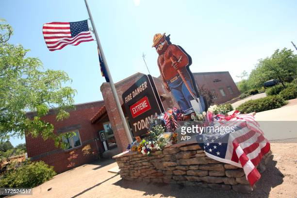 An American flag flies at half staff near an extreme fire danger sign outside of the Prescott Fire Station 1 on July 2 2013 in Prescott Arizona The...