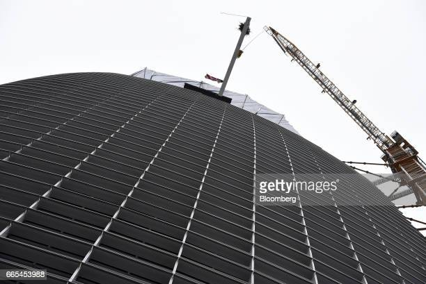 An American flag flies from the final steel beam being hoisted up to the top of the building during a topping off ceremony for the Salesforce Tower...