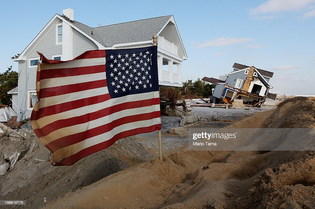 An American flag flies in front of the ruins of a destroyed home on November 21, 2012 in Mantoloking, New Jersey. Mantoloking was one of the hardest hit areas by Superstorm Sandy.