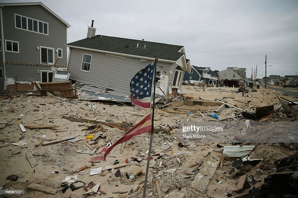 An American flag flies near homes that remain damaged and mostly untouched since Superstorm Sandy hit the coastline, May 5, 2013 in Ortley Beach, New Jersey. Superstorm Sandy slammed into the New Jersey coastline six-months ago causing approximately $29.4 billion in damage.