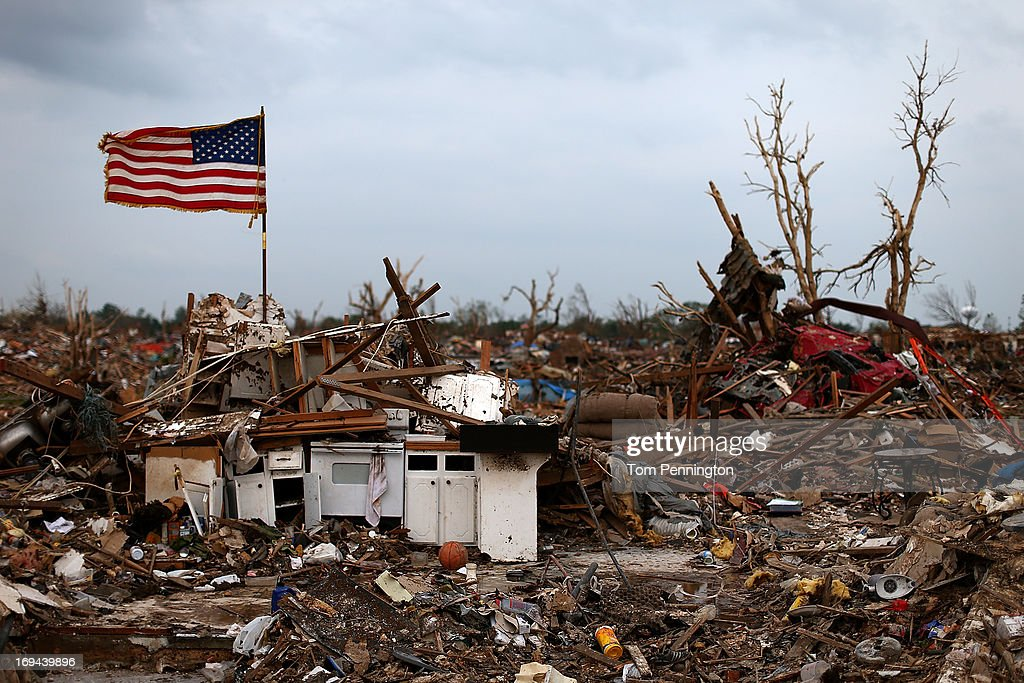 An American flag flies over the rubble of a destroyed neighborhood on May 24, 2013 in Moore, Oklahoma. The tornado of EF5 strength and two miles wide touched down May 20 killing at least 24 people and leaving behind extensive damage to homes and businesses. U.S. President Barack Obama promised federal aid to supplement state and local recovery efforts.