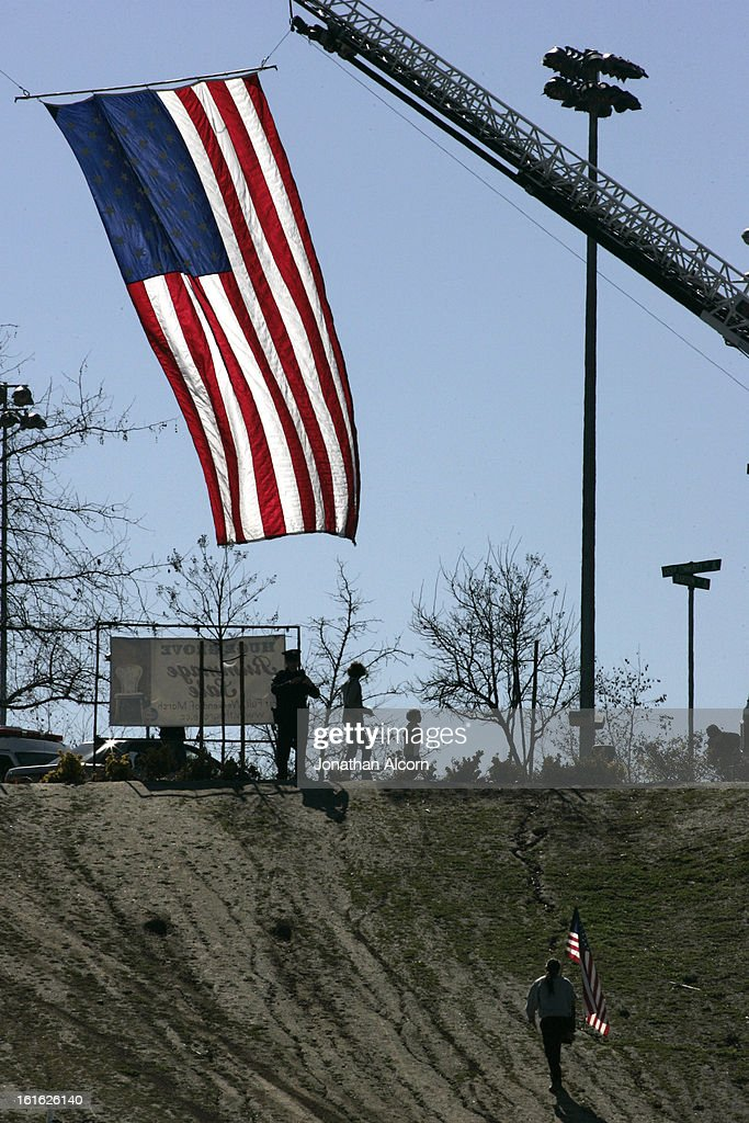 An American flag hanging from a fire department vehicle stands in honor outside the funeral for Riverside police Officer Michael Crain at Grove Community Church in Riverside, California, February 13, 2013. Officer Crain was allegedly killed by ex LAPD officer Chris Dorner on February 7, 2013.
