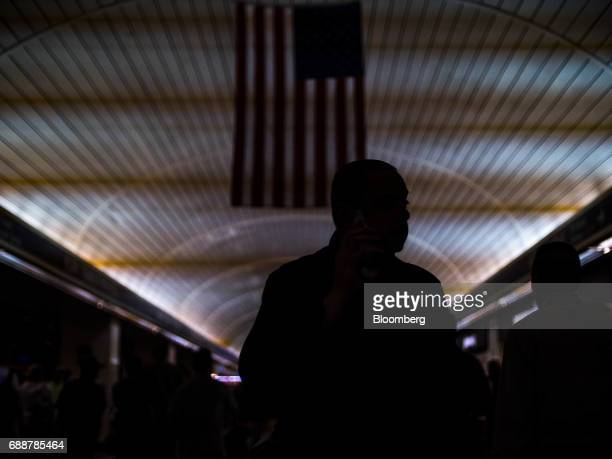 An American flag hangs above a commuter walking through the Long Island Railroad Co concourse inside Pennsylvania Station in New York US on Friday...