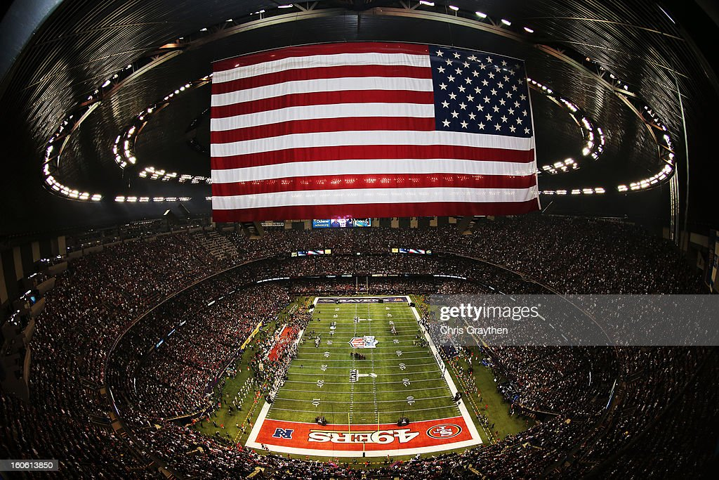 An AMerican Flag hangs above the stadium as Jennifer Hudson performs 'America the Beautiful' with the Sandy Hook Elementary School Chorus during Super Bowl XLVII between the Baltimore Ravens and the San Francisco 49ers at the Mercedes-Benz Superdome on February 3, 2013 in New Orleans, Louisiana.