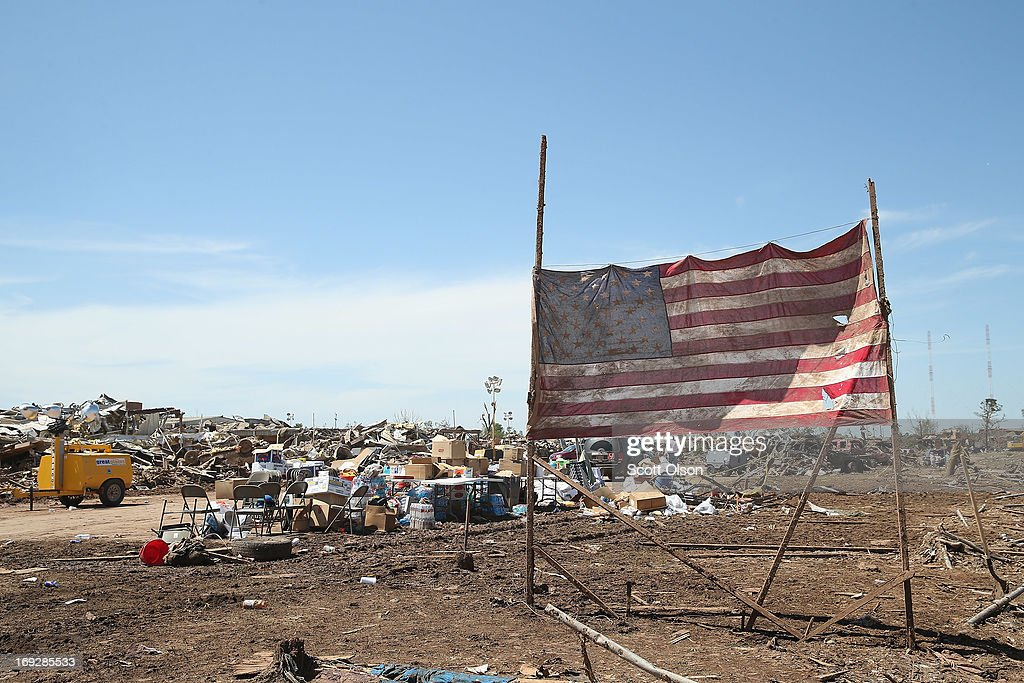 An American flag hangs in front of the destroyed Plaza Towers Elementary School after it was hit by a tornado that ripped through the area on May 22, 2013 in Moore, Oklahoma. Seven children died in the school during the tornado. The tornado of at least EF4 strength and two miles wide touched down May 20 killing at least 24 people and leaving behind extensive damage to homes and businesses. U.S. President Barack Obama promised federal aid to supplement state and local recovery efforts.