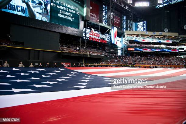 An American Flag is displayed during the National Anthem prior to the National League Wild Card game between the Arizona Diamondbacks and Colorado...