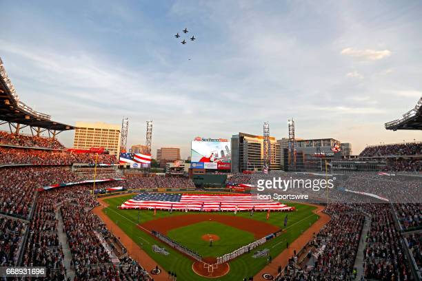 An American flag is displayed in the outfield as a flyover takes place during the singing of the national anthem prior to the Atlanta Braves home...