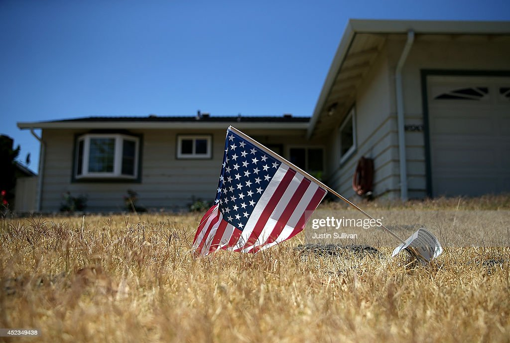 An American flag is displayed on a dead lawn in front of a home on July 18, 2014 in Fremont, California. As the severe drought in California contiues to worsen, the State's landscape and many resident's lawns are turning brown due to lack of rain and the discontinuation of watering.
