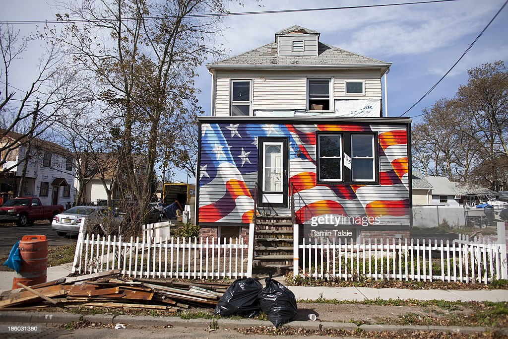 An American flag is painted on a house damaged during Hurricane Sandy on October 27, 2013 in Staten Island borough of New York City. Hurricane Sandy made landfall on October 29, 2012 near Brigantine, New Jersey and affected 24 states from Florida to Maine and cost the country an estimated $65 billion.