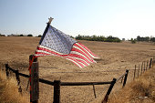 An American flag is posted on a fence in front of a dry unplanted field on August 8 2014 in Lodi California As the severe drought in California...