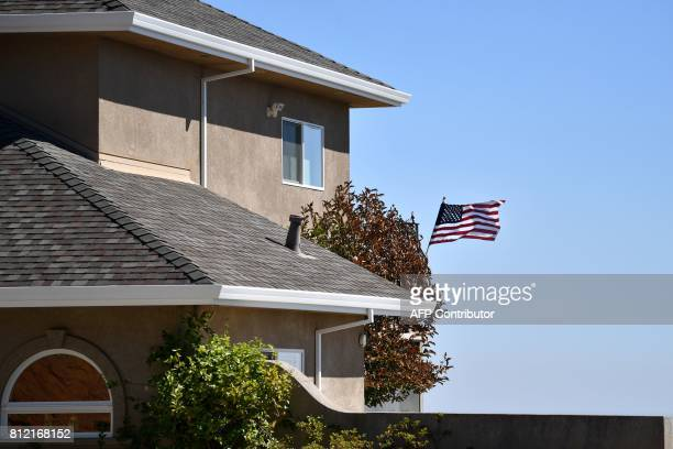 An American flag is seen blowing in the wind on a saved house where firefighters were seen rescuing the flag from impending flames during the Wall...