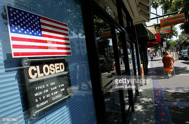 An American flag is seen next to a closed sign on a business in the Mission District as thousands closed their businesses to protest for immigrant...