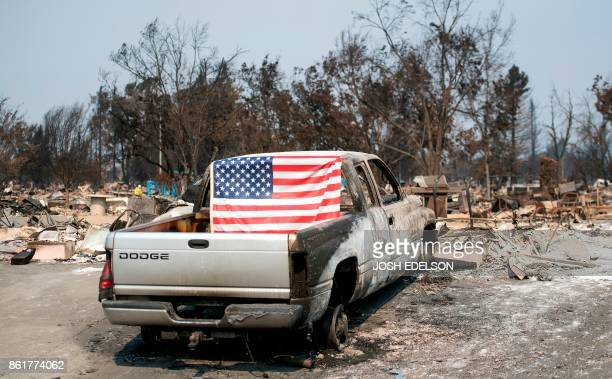 An American flag is seen on a burned out truck in Santa Rosa California on October 15 2017 The death toll from California's wildfires rose to 40...