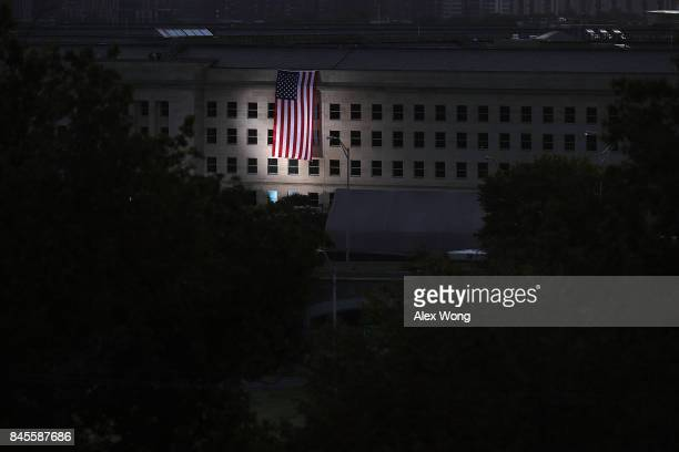 An American flag is unfurled on the side of the Pentagon to commemorate the anniversary of the 9/11 terror attacks September 11 2017 in Arlington...
